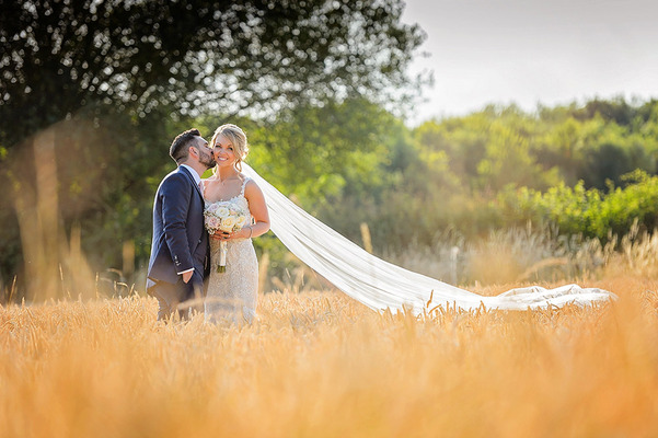 Groom kissing bride with long veil on the cheek  in field