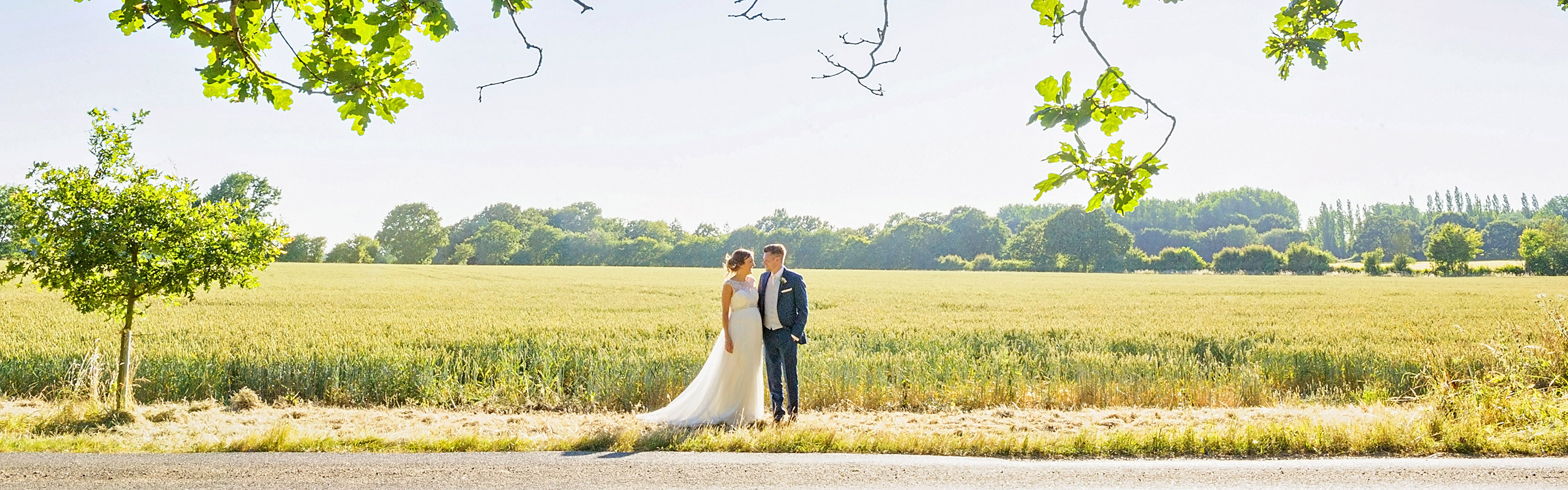 Wedding couple in front of sunny field at Dove Barn